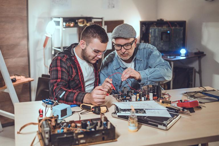 Two people working on electronics together.